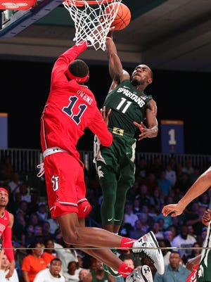 Michigan State guard Tum Tum Nairn dunks over St. John's forward Tariq Owens during of their Battle 4 Atlantis quarterfinal in the Imperial Arena at the Atlantis Resort in the Bahamas, not far from where Nairn grew up.