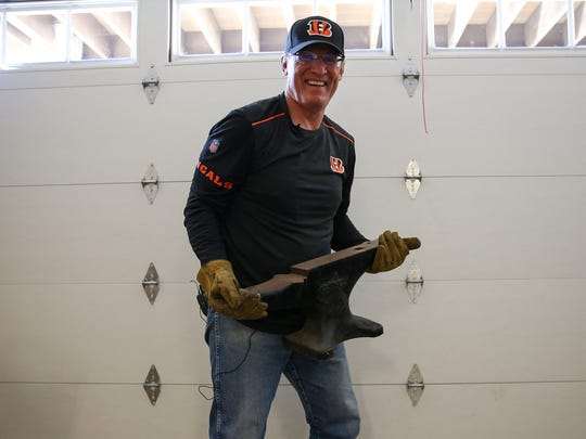 Former Cincinnati Bengals defensive tackle Tim Krumrie, pictured at his home in Steamboat Springs, Colorado, carrying an anvil he used for strength conditioning during his playing days, suffers from a damaged frontal lobe in his brain, but he has sought treatment that he now says has improved his health.