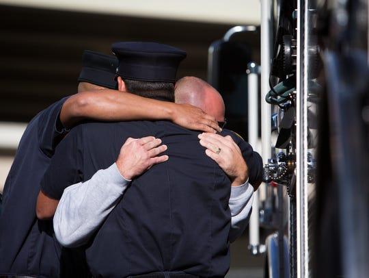 Lt. John Cawthray hugs fellow firefighters who fought