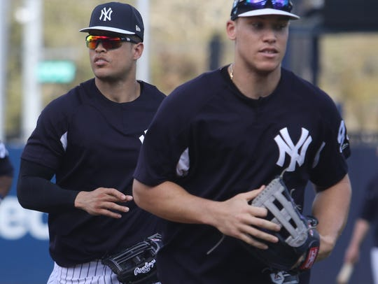 Giancarlo Stanton and Aaron Judge run in from the outfield