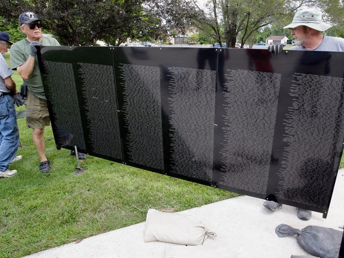 James Sundee of Plymouth, left, and Bob Dobek, the site manager for The Wall That Heals, assemble the panels for a half-size replica of the Vietnam War Memorial in Washington, D.C. Tuesday August 19, 2014 in Sheboygan. The wall replica is making a visit to Sheboygan County Veterans Memorial.