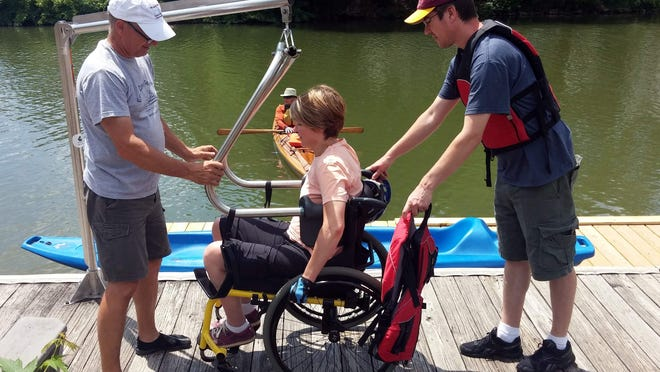 Kerrie Giesen gets some help from Erie Canal Boat Company owner Peter Abele (left), her husband Dave and the Hoyer Lift, to get into a kayak.