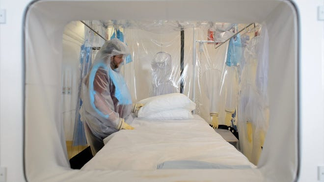 A nurse wears protective clothing as he demonstrates on Aug. 6 the facilities in place at the Royal Free Hospital in north London in preparation for a patient testing positive for the Ebola virus.
