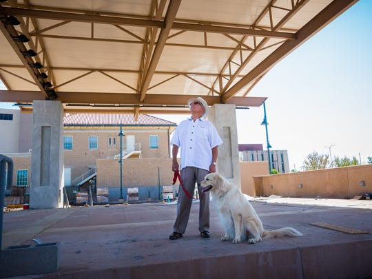 """Former Las Cruces Mayor Rubén Smith examines the new downtown plaza's stage while walking with his dog Lilly. He envisions the plaza as """"a place for anything and everything."""""""