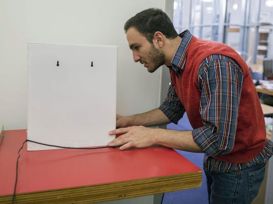Massachusetts Institute of Technology researcher Fadel Adib sets up the RF-Capture device behind a wall in a room at MIT in Cambridge, Mass. RF-Capture uses WiFi signals to see through walls, and is able to sense where a person is in a room, if a person is sitting, moving or has fallen. It also can sense heart rate and breathing rate.