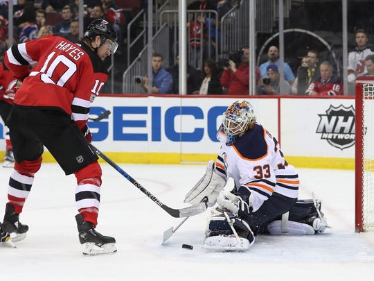 Edmonton Oilers goalie Cam Talbot (33) makes a save while New Jersey Devils right wing Jimmy Hayes (10) looks for the rebound during the second period at Prudential Center.