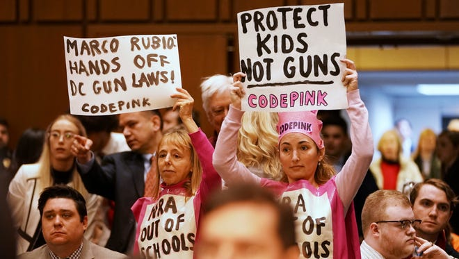 Protesters from the group, Code Pink, hold up signs about guns as Sen. Marco Rubio, R-Fla., and Sen. Bill Nelson, D-Fla., arrive to testify at a Senate Judiciary Committee hearing on the Parkland, Fla., school shootings and school safety, Wednesday, March 14, 2018, on Capitol Hill in Washington.