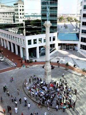 Protesters gather and chant slogans at the base of the Confederate Monument in downtown Norfolk, Va., on Wednesday, Aug.  16, 2017.