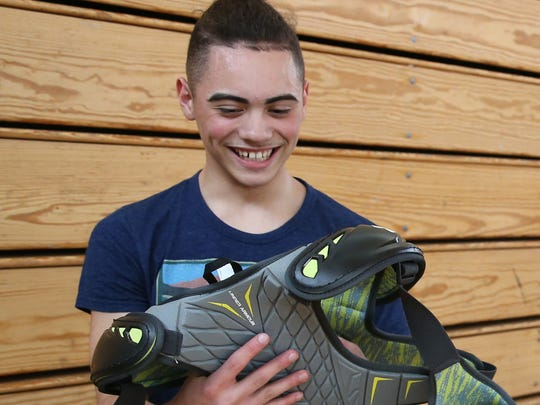 World of Inquiry student Edgardo Morales is all smiles as he tries on his new lacrosse pads at East High School Tuesday, April 11, 2017.  The Rochester Knighthawks and Diamond Packaging donated Under Armour gear to the high school lacrosse team as part of their ongoing program of starting boys and girls varsity lacrosse in the city next school year.