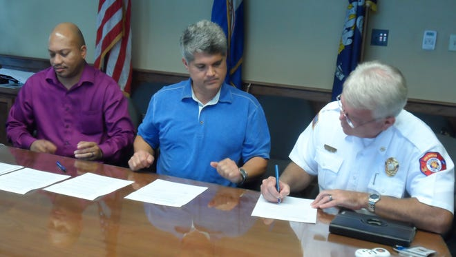 Alexandria Mayor Jacques Roy (center) watches Monday as Alexandria Fire Prevention Chief Larry King (right) signs an attestation to Roy's executive order that could lead to the city taking steps to make  the vacant Weiss & Goldring building on Third Street secure. City Attorney Chuck Johnson (left) also signed the order.