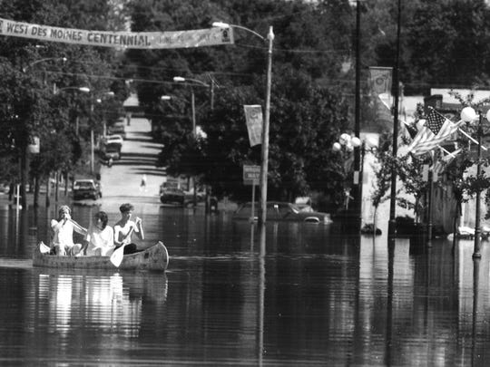Canoers paddle down Fourth Street in the Valley Junction area of West Des Moines on Monday, July 12, 1993.