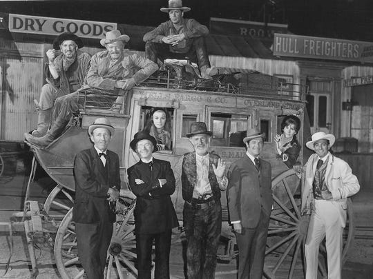 Alex Cord sits atop the stage with the cast of the