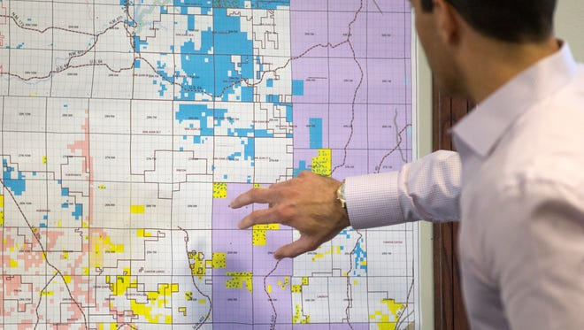 Jay Paul McWilliams, president of LOGOS Resources, looks over a map, Tuesday, Dec. 12, 2017 during an inteview at Logos Resources, LLC in Farmington.