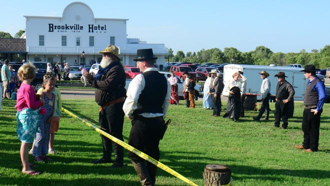 Visitors watch as the Old Abilene Town Gunfighters perform outside of the Brookville Hotel in 2015. The Brookville Hotel that was to reopen in June with new ownership and a new name of Legacy Kansas may  not be able to as the restaurant has about $160,000 with unpaid tax and penalties to Dickinson County.