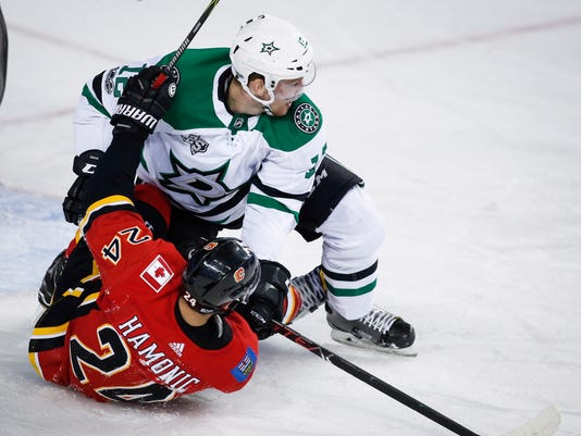 Dallas Stars center Radek Faksa (12) from the Czech Republic, holds down Calgary Flames defenseman Travis Hamonic (24) during the second period of an NHL hockey game, Friday, Oct. 27, 2017 in Calgary, Alberta. (Jeff McIntosh/The Canadian Press via AP)
