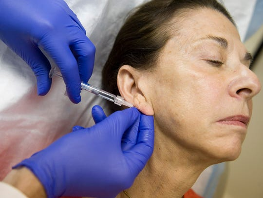 Barbara Corea gets a Restylane injection in her ear