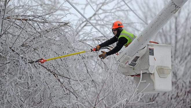 Andrew Powers, an arborist with Asplundh Tree Experts, clears power lines from iced branches along Mayflower Heights Drive in Waterville, Maine, on Dec. 23, 2013.
