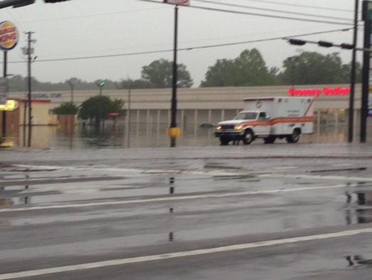 An ambulance heads down Palafox Street near a flooded Brent Lane Wednesday morning.