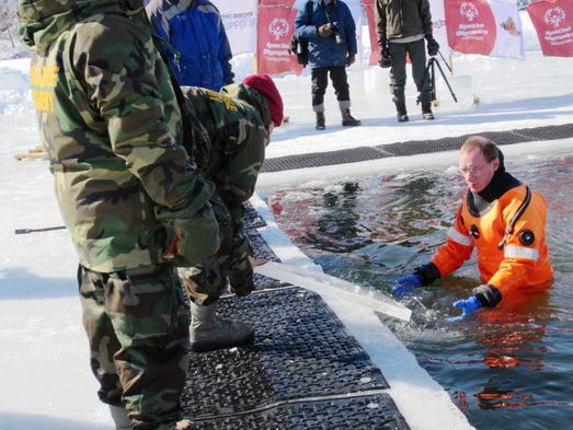 Two-and-a-half inches of ice developed on the Polar Plunge hole overnight, delaying the plunge until divers and volunteers removed it at the Polar Plunge for Special Olympics Wisconsin on Sunday, Feb. 23, 2014 at Half Moon Beach in Eau Claire.