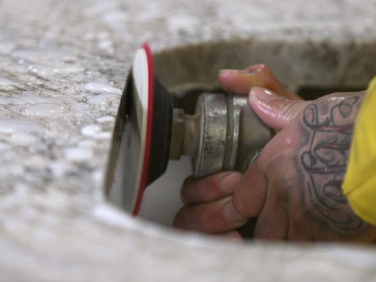 A hand grinder is used to finish the edges after cutting a slab of granite.