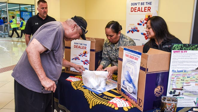 Tamuning resident Many Ulloa, left, submits various outdated medications to Guam National Guard Counterdrug Progam's Staff Sgt. Ruth Aguon during the 15th National Prescription Drug Take Back Day collection at the Agana Shopping Center on Saturday, April 28, 2018. The biannual collection of the drugs is an effort to rid homes of potentially dangerous expired, unsed and unwanted prescription drugs, according to a U.S. Attorney's Office release.