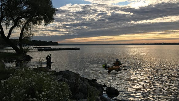 Swimmers, accompanied by a kayaker, get ready to ply