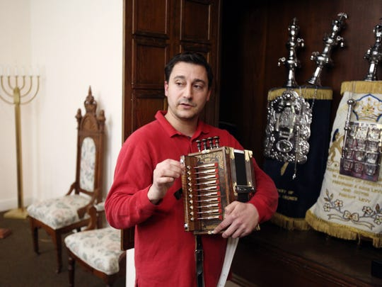 Musician Daniel Gale holds his accordion while talking about the Torah Scrolls at Temple Shalom on Wednesday.
