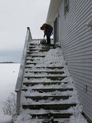 Eddie Chandler shovels steps in Crisfield on Thursday