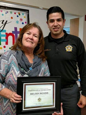 Hidalgo County Sheriff's Office Chief Administrator Edgar Gomez, right, presents Melody Richins of Hidalgo Medical Services with an appreciation certificate from the sheriff's office signed by Sheriff Warren Walter.
