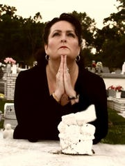 Allyson Schram, a medium, prays at a cemetary in Arnaudville, April 30, 2013.