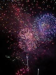 Firework colors stand out against the dark sky over