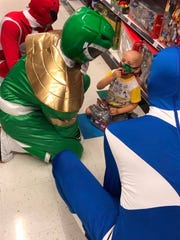 Grayson Dodd visits with the Power Rangers during a shopping trip to Toys R Us.