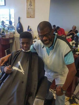 Robert Tyson, owner of Smove Cuts Unisex Salon on U.S. 1, hopes the Connecting Children with Reading Community Bookshelf will reach his young clients with the written word