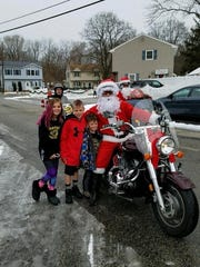One of the motorcycle Santas, poses for a photograph with some Wanaque children on Dec. 17, 2017.