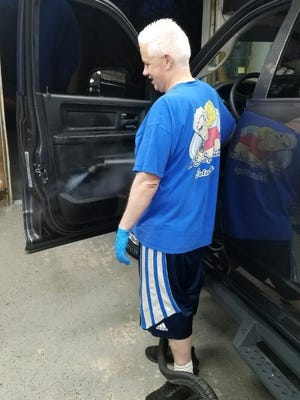 Ed Lawrence, owner of E&C Spitshine Detailing in Middletown uses hot steam to sanitize the interiors of vehicles.