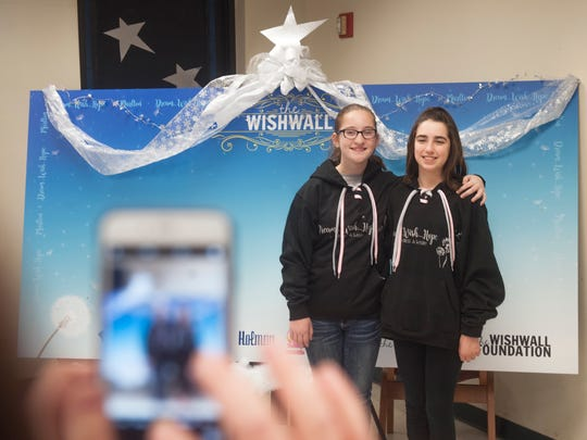 Girl Talk Marlton members (from left) 12-year-old Emily Izzo of Marlton and 12-year-old Mia Mulholland of Marlton stand in front of the Wishwall that they and other members set up at the Evesham Township Library.  On Saturday, the Wishwall will be unveiled and dedicated in memory of singing star Christina Grimmie, a Marlton native who was killed last summer.