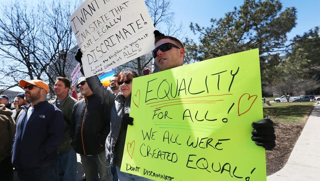 Jeremy Greenwood (right), and Colleen Gannon, both Indianapolis, held signs at the rally on the steps of the Statehouse in Indianapolis where several thousand opponents of Indiana's recently passed Religious Freedom Restoration Act (RFRA) held a rally on Saturday, March 28, 2015.
