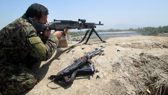 An Afghan security force member aims his weapon during a battle with Taliban insurgents in the Chahardara district of Kunduz province north of Kabul on May 3.