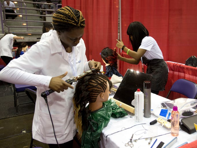 Shaqunda Mc Corvey , left,  and Charlene Destine, right, puts their hair design skills to the test during a competition at the Skills USA Conference at the Pensacola Bay Center Monday morning April 28, 2014.