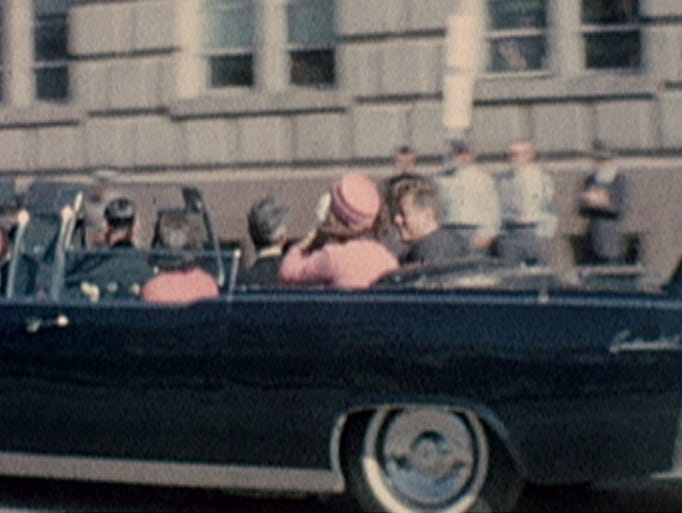President John F. Kennedy and his wife, Jacqueline, ride in a motorcade moments before the president was shot Nov. 22, 1963, in Dallas.