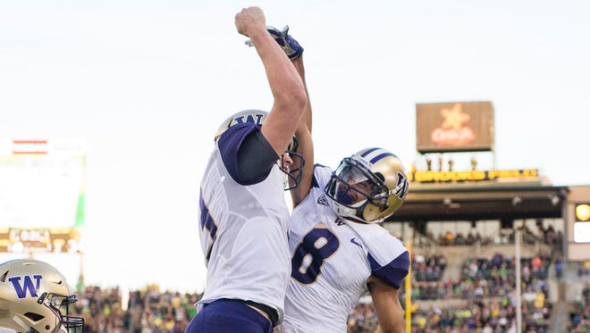 Washington quarterback Jake Browning (3) celebrates with wide receiver Dante Pettis (8) after scoring a touchdown during the second quarter in a game against the University of Oregon Ducks at Autzen Stadium.