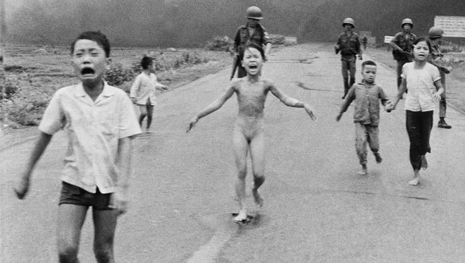 In this June 8, 1972, file photo, 9-year-old Kim Phuc, center, runs with her brothers and cousins, followed by South Vietnamese forces, down Route 1 near Trang Bang after a South Vietnamese plane accidentally dropped its flaming napalm on its own troops and civilians. The terrified girl had ripped off her burning clothes while fleeing. In late September 2015, Phuc, 52, began a series of laser treatments at the Miami Dermatology and Laser Institute to smooth and soften the pale, thick scar tissue that she has endured for more than 40 years.