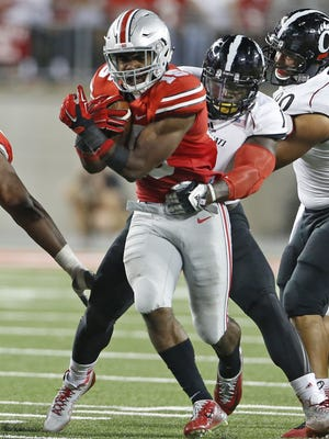 Ohio State University's Ezekiel Elliott, 15, is tackled by University of Cincinnati's Jeff Luc during the third quarter of their game played at Ohio State in Columbus, Ohio Saturday September 27, 2014.