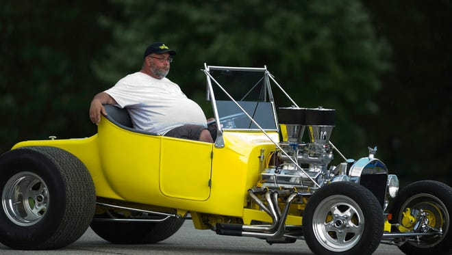 Ralph Davis of Martinsville, Ind., waits for a parking spot under a canopy in his 1923 T-Bucket Chevrolet with a 383 stroker motor at the Frog Follies Friday evening. A small storm was spitting out rain and lightning and chased many of the more than 3,500 registered participants out of the Vanderburgh County 4-H Fairgrounds to look for cover.