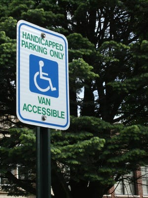 A sign for van-accessible handicapped parking is shown outside a Cedar Rapids school on May 12, 2016.