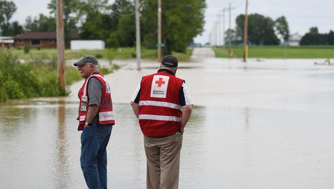 Red Cross volunteers Steve Switzer, left, and Karl Gingrich look over the flooding June 17 on Marion Township 207, just west of Marion Township 244 near the Findlay Reservoirs. (Randy Roberts/The Courier via AP)