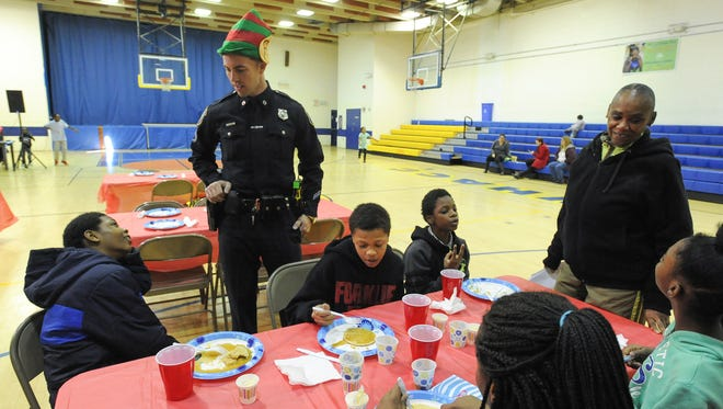 Senior Corporal Thomas Oliver with the Wilmington Police Department talks with kids who came to eat breakfast which the police department cooked at West Center City's Hicks Anderson Center on Saturday morning.