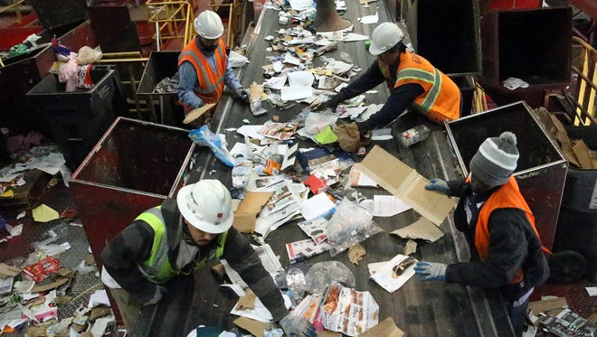 Workers separate cardboard from paper traveling on a conveyer belt at the Friedman Recycling Co. plant at 5835 Wren Ave. in Northeast El Paso Monday.