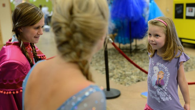 "Five-year-old Cecilia Huuki, of Marquette, Mich. talks to Princess Anna (at left, portrayed by thirteen-year-old Abby Bailey, of De Pere) and Queen Elsa (portrayed by seventeen-year-old Lizzie Grunwald, of Green Bay) from ""Frozen"" at The Children's Museum of Green Bay on Sunday."