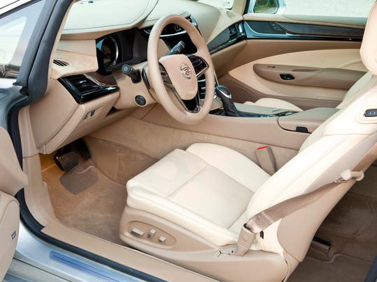 Inside the 2014 Cadillac ELR, cut-and-sewn leather and suede microfiber upholster the dash and doors. A motorized cupholder cover takes care of your beverage.